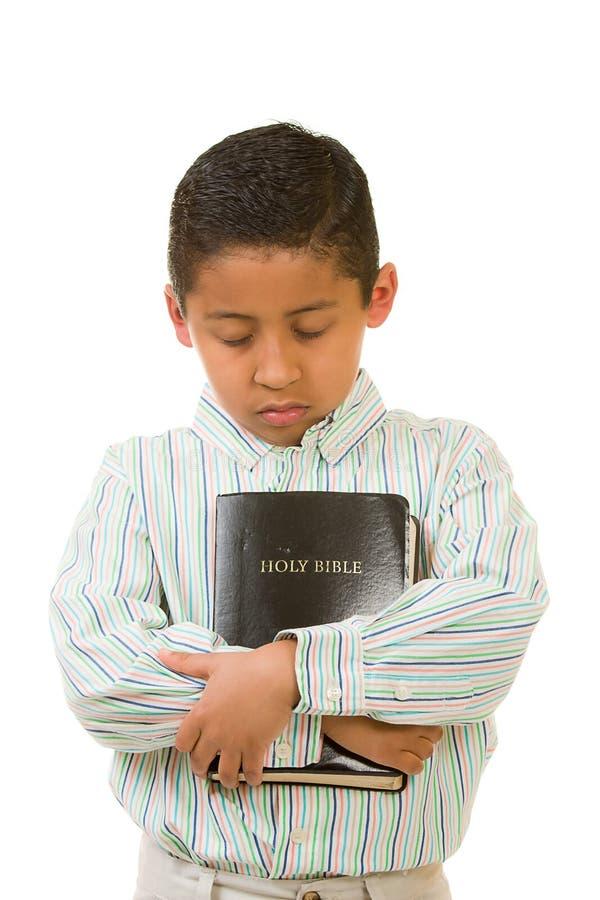 Child Praying While Hugging Bible stock image