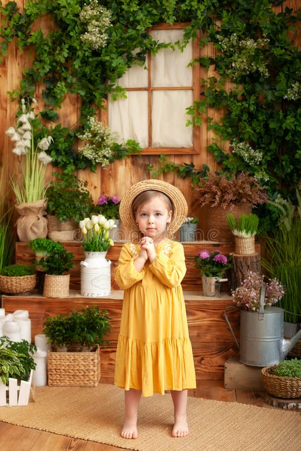 Child praying. Little girl hand praying, Hands folded in prayer concept for faith, spirituality and religion. A little girl is wor. Th in backyard of wooden stock image