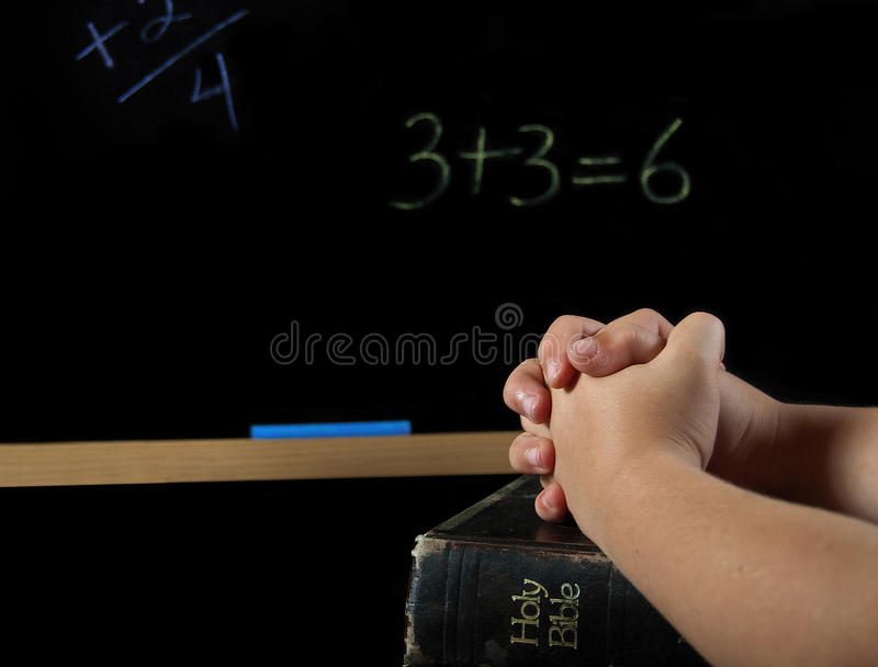 Child praying in school. Child's hand folded in prayer on a Holy Bible with chalkboard royalty free stock images