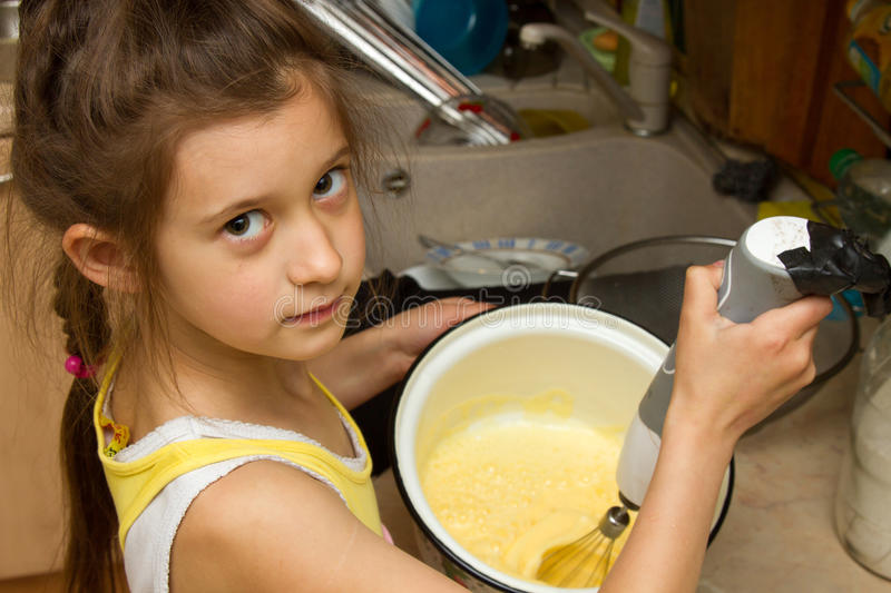 Child preparing cookies in kitchen. Making of a cream for home-made cakes on a mixer food stock photo