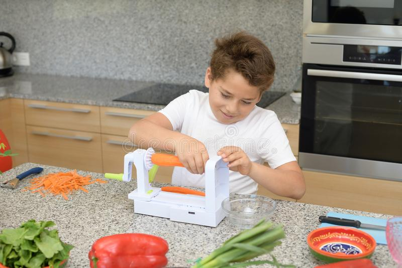 Child preparing lunch. Putting carrots in a manual machine stock images