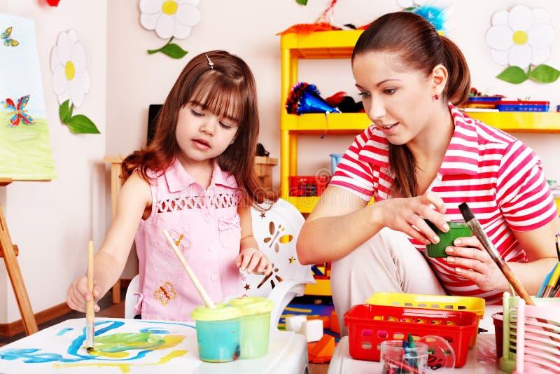 Child in preschool with teacher draw. stock image