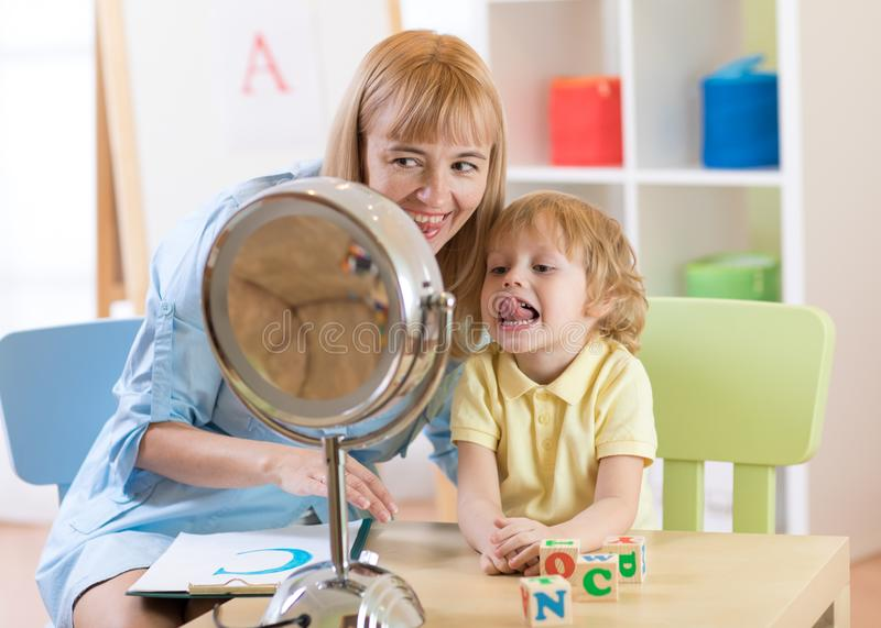 Cute child boy at speech therapist office. Kid makes tongue exercises together with teacher. Child preschooler boy at speech therapist office. Kid makes tongue royalty free stock photos