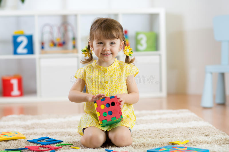 Child preschooler girl plays logical toy learning shapes and colors at home or nursery stock photo