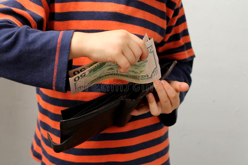 Child, preschooler, primary school student, puts money, banknotes, dollars, euros in a leather wallet, hands close-up stock photo