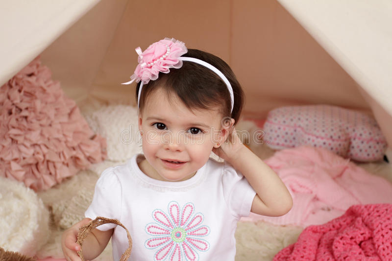 Child Pretend Play: Dress Up Costume Headband and Teepee Tent. Toddler child, kid, engaged in pretend play with a pink flower headband and teepee tent stock photography