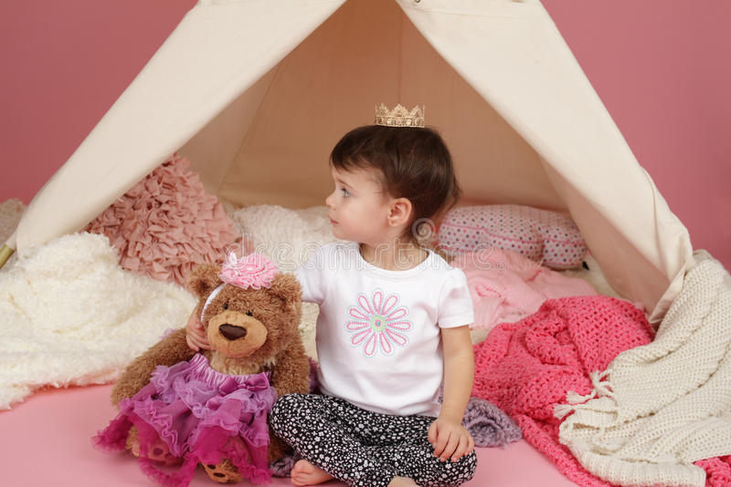 Child Pretend Play: Princess Crown and Teepee Tent. Toddler child, kid, engaged in pretend play with princess crown and teepee tent royalty free stock image