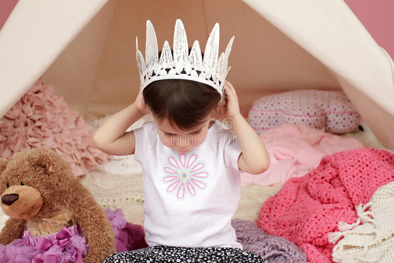 Child Pretend Play: Princess Crown and Teepee Tent. Toddler child, kid, engaged in pretend play with princess crown and teepee tent stock images