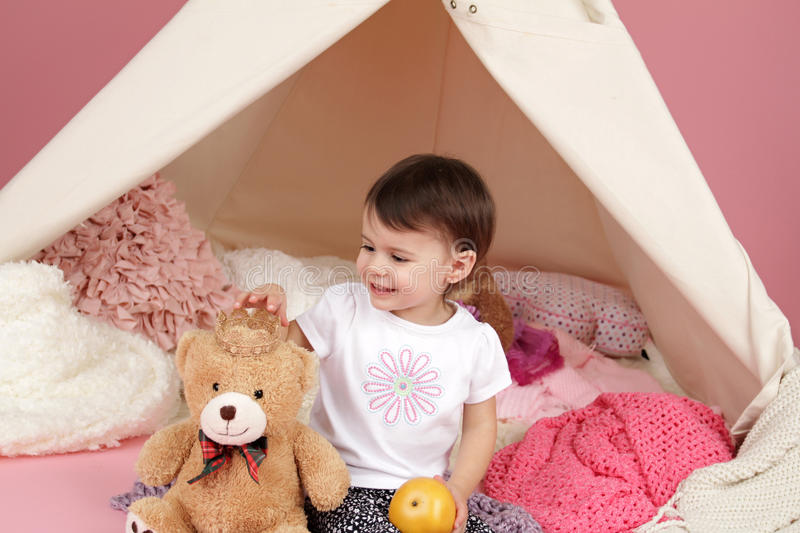 Child Pretend Play: Princess Crown and Teepee Tent. Toddler child, kid, engaged in pretend play with princess crown and teepee tent stock photo