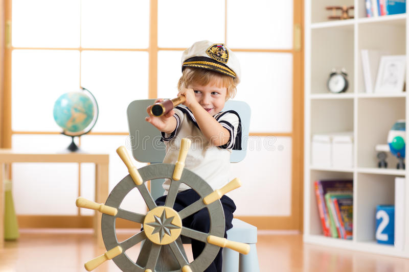 Child pretend to be sailor. Kid boy looking through spy glass playing at home. stock image