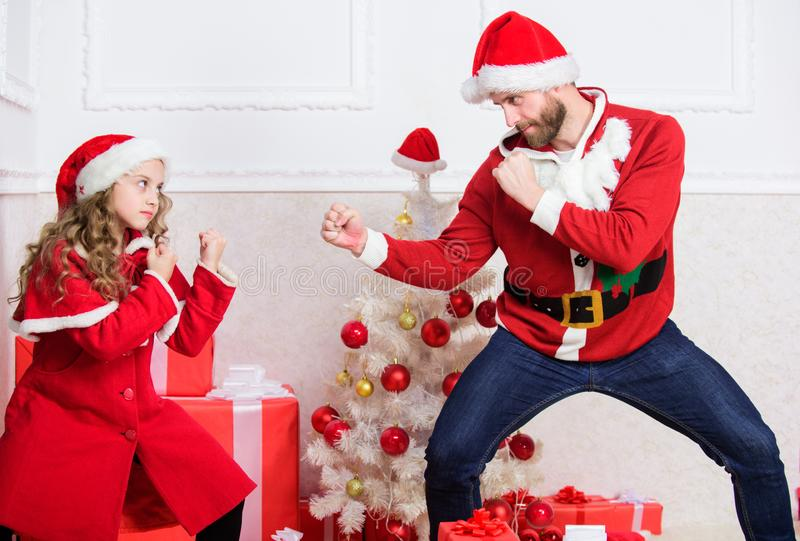 Child pretend to fight for christmas gifts. Christmas games. Make it fun. Kid cute girl play with father near christmas royalty free stock images