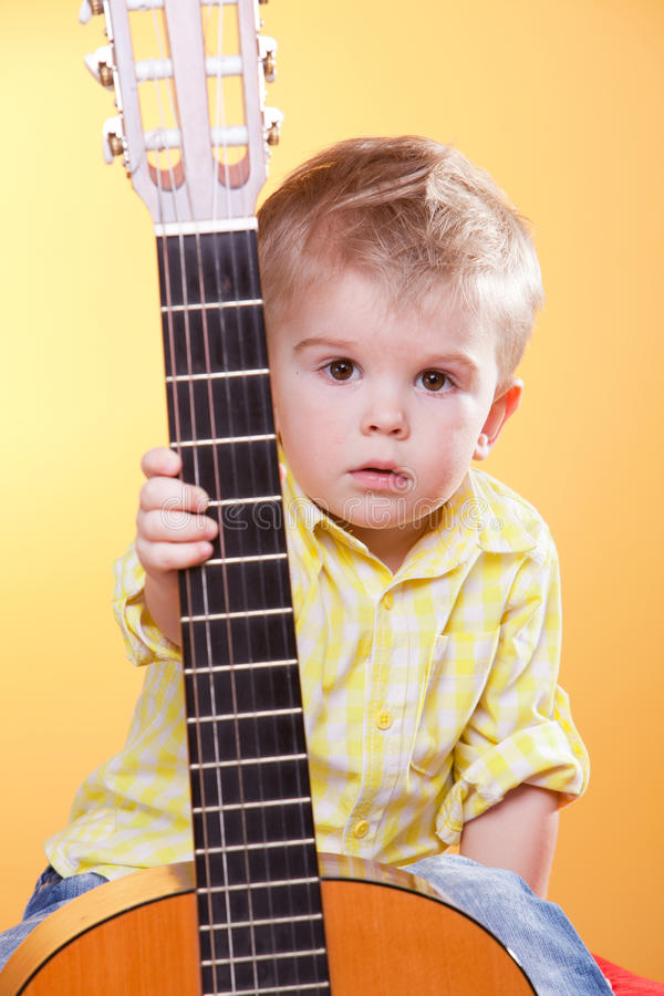 Child proposing play the guitar. Looking at camera stock image