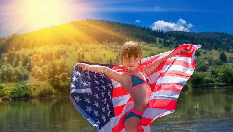 Child protection in USA concept. Cute happy young beautiful girl dancing with the flag of United States of America. Horizontal royalty free stock images