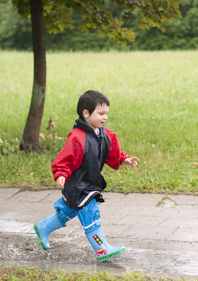 Download Child in puddle stock photo. Image of playing, rainboots - 25284300
