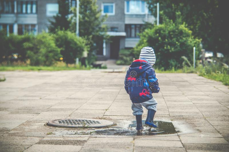 Child in puddle, city fun stock photography