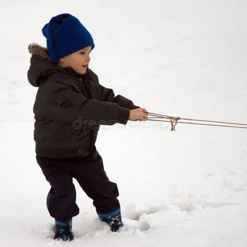 Child pulling string of sled royalty free stock photo