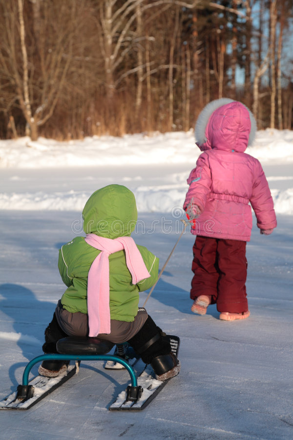Child Pulls Another On Snow Scooter From Back Royalty Free Stock Photo