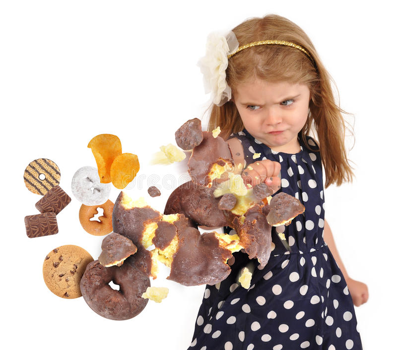 Child Punching Unhealthy Junk Food Snakes on White. A little child is punching a chocolate donut as cookies and junk food are coming to her for a health or stock images