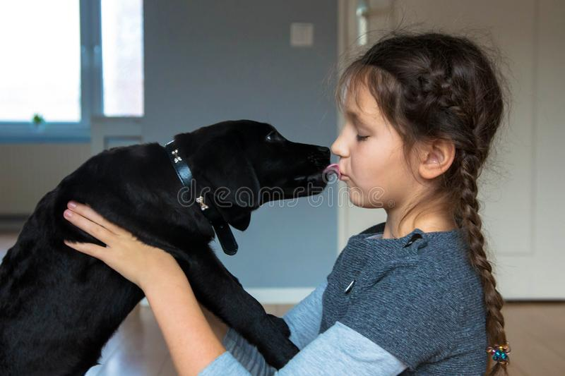 Child and puppy kiss. Dog man`s best friend royalty free stock photography