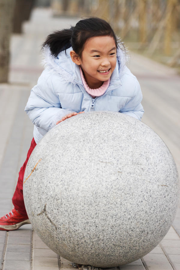Download Child push stone ball stock image. Image of girl, active - 24118603