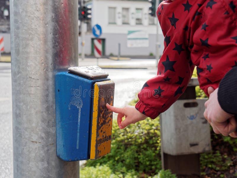 Child pushing button at pedestrian light royalty free stock photos