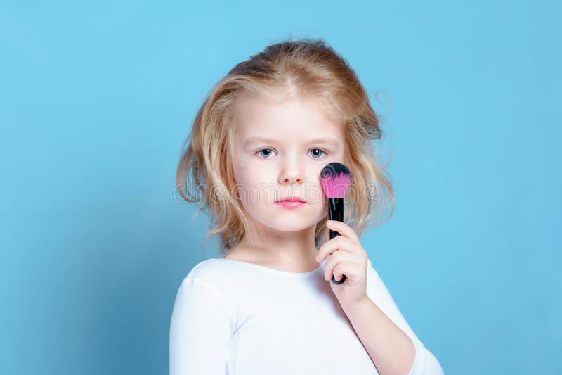 The child put a makeup brush to his cheek. Beautiful girl with blond hair, little model. Bright advertising photography. stock images