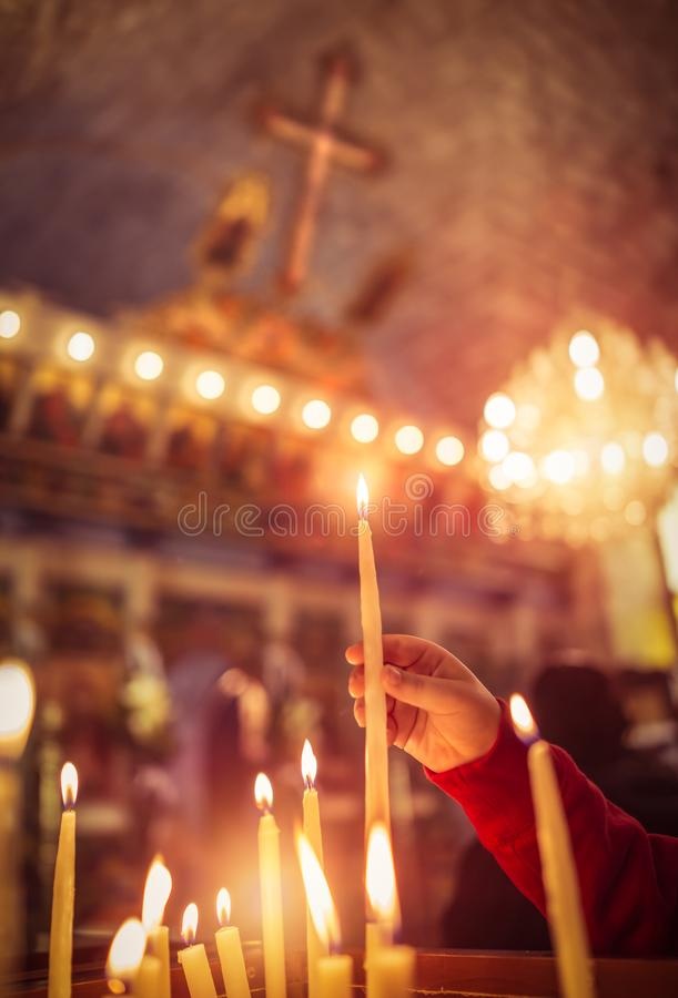 Child puts a candle in the church stock photography