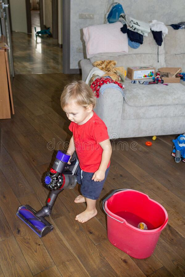 A child puts the house in order with a vacuum cleaner in one hand and a bucket of water and a rag to wash the floor in the other. A child puts the house in stock photos