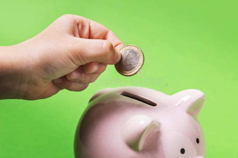 A child puts one euro in a piggy bank. We teach children from childhood to save for retirement and rely only on themselves stock photography