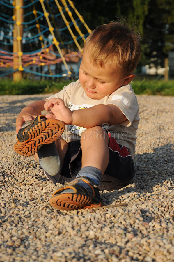 Child putting his shoes on. Little child, a young boy, sitting on the ground in a playground and putting his shoes on stock photo