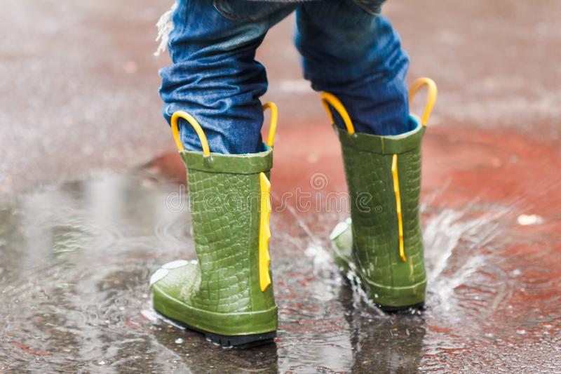 Child with rain boots jumps into a puddle stock photography