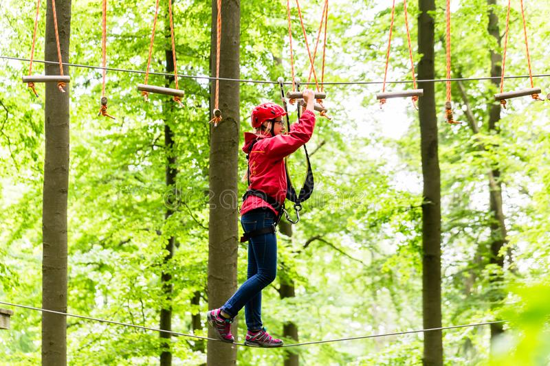Child reaching platform climbing in high rope course. In forest stock image