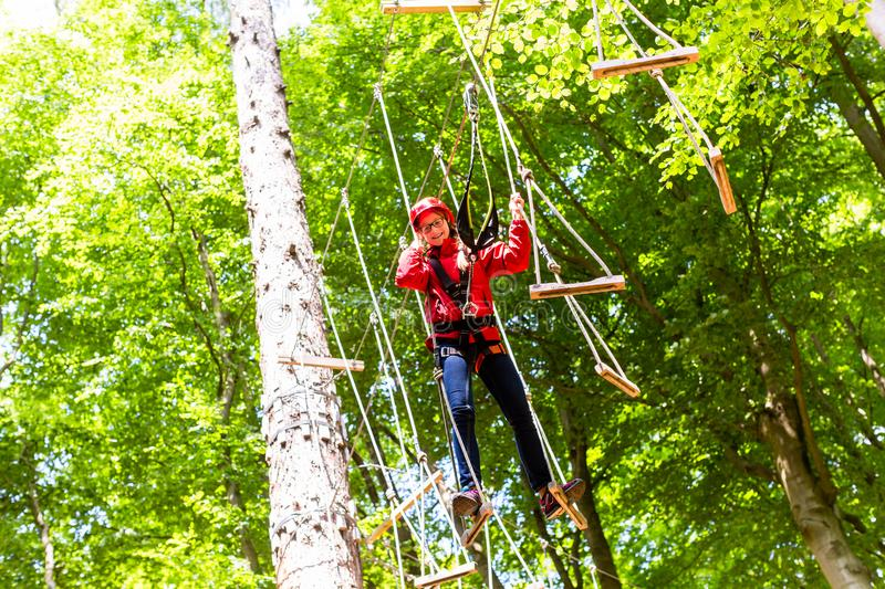 Child reaching platform climbing in high rope course. In forest royalty free stock image