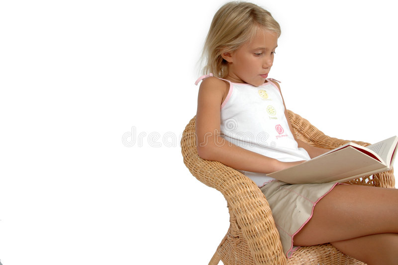 Child Reading. Image is for the importance of a child learning to read. White background, copy space to the left. Child sitting in a chair reading stock images