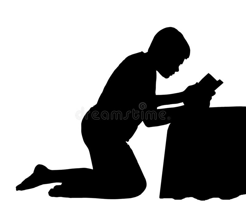 Child Reading Bible next to Bed stock photo