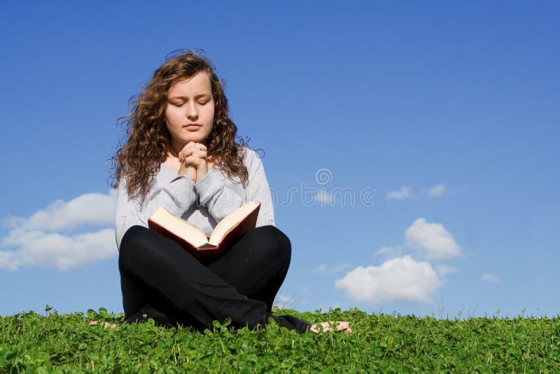 Child reading bible praying stock image