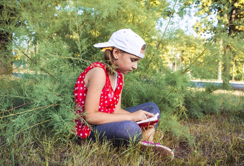 Child reading book or bible outdoors . Cute little girl reading the Bible . Young Child`s Hands Praying on Holy Bible . Inner world of the child . Meditation royalty free stock photo