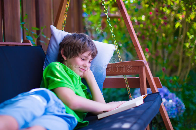 Child reading a book in the garden. Happy school boy reading a book in the backyard. Child relaxing in a garden swing with books. Kids read during summer royalty free stock photography