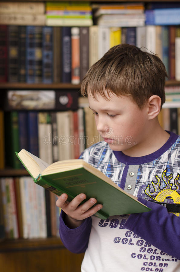 Child reading book at home. Boy in library royalty free stock photography