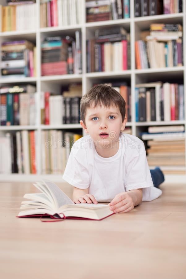 Child reading a book at home. Looking at camera. stock photo