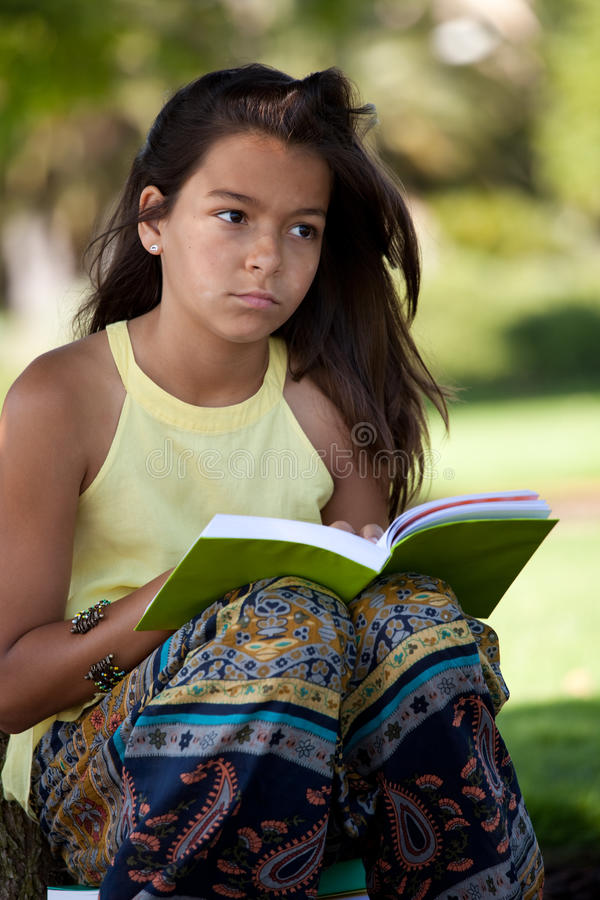Child reading a book at the park. Young female child reading a book at the park royalty free stock photo