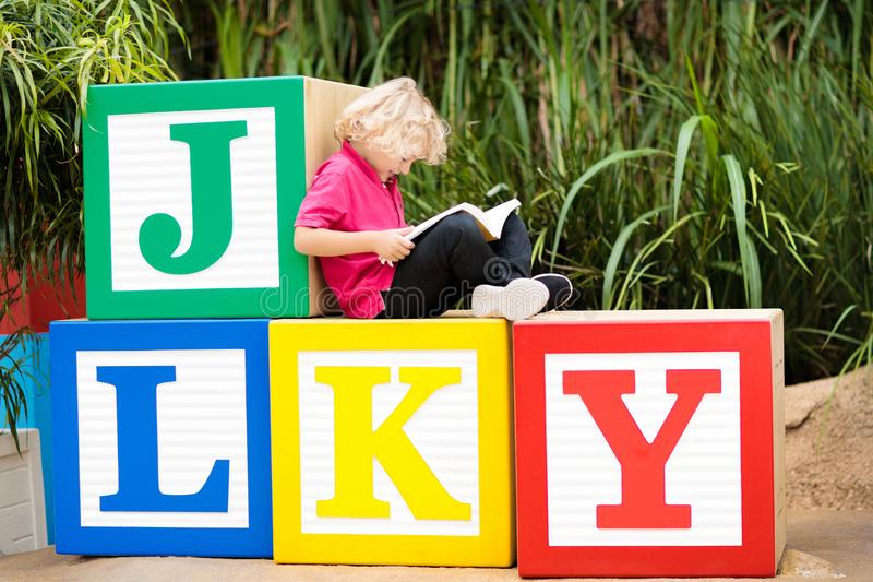 Child reading book in school yard. Kid learning abc letters. Little boy sitting on wooden toy blocks with alphabet in preschool or royalty free stock images