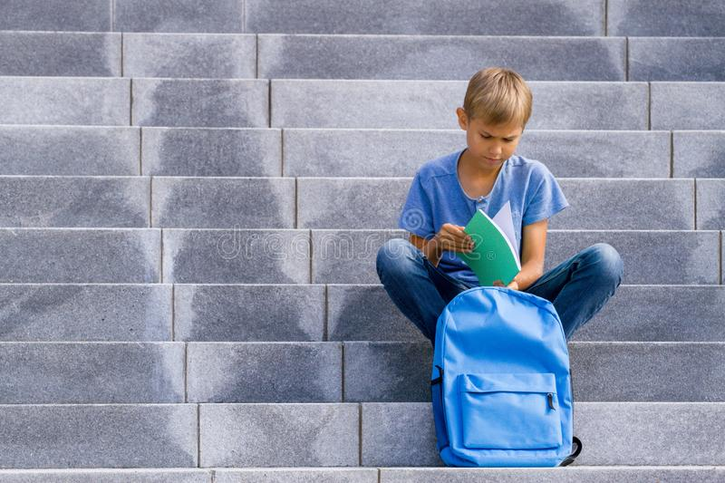 Boy reading book sitting on the stairs outdoors stock photos