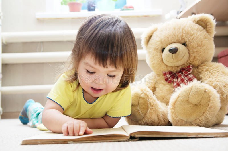 Child reading book for toy teddy bear, little girl learning and stock photography