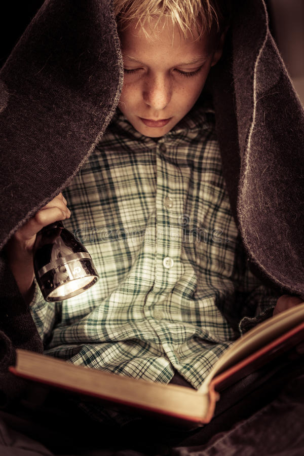 Child reading book under covers with flashlight. Cute serious child in green flannel shirt reading hard cover book under blanket covers with flashlight stock images