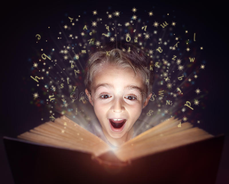 Child reading a magic story book royalty free stock photo