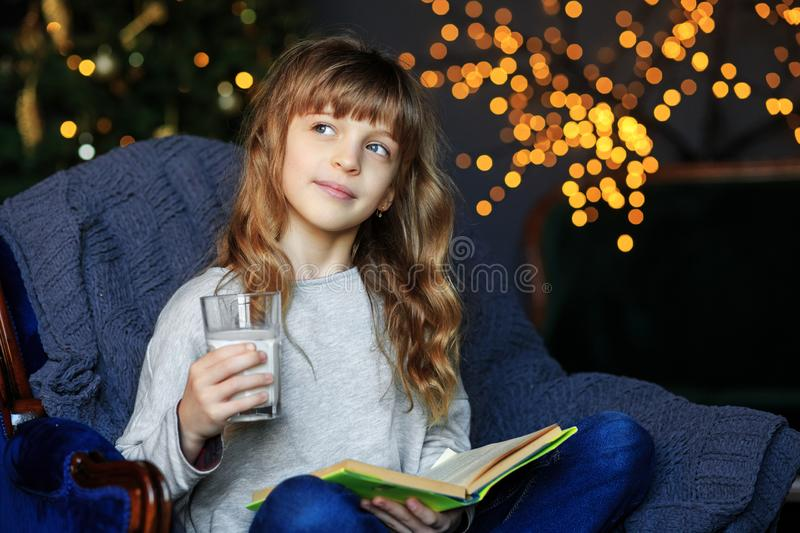 Child reads a book and dreams on Christmas Eve. Tasty milk. The concept of holidays, merry christmas, winter and childhood stock image