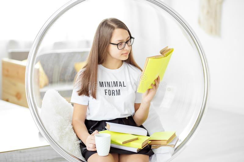 The child reads an interesting book with glasses. Drinking tea. Concept of education, hobby and study and world book day stock image