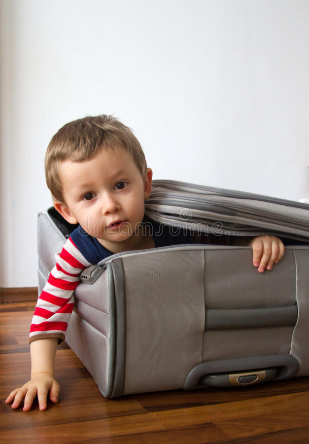 Child ready to travel. Funny child in a suitcase all packed and ready to travel royalty free stock photography
