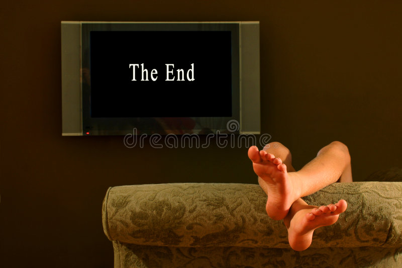 Child reclining feet up watching the end of a movie stock photo